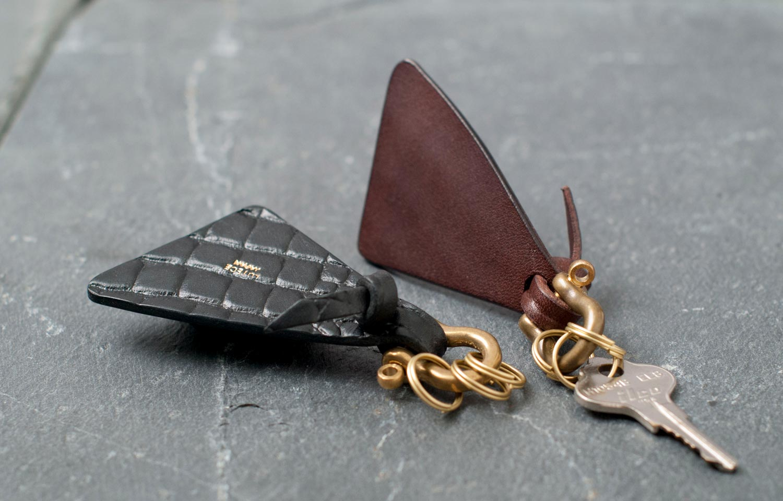 クロコ模様が見える表面とつるんとした裏面と革を張り合わせた側面がわかるキーホルダーの写真
