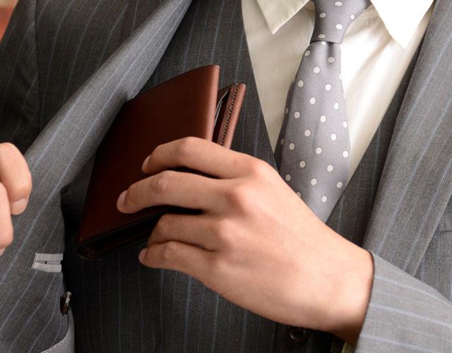 二つ折り財布を内ポケットに入れる様子